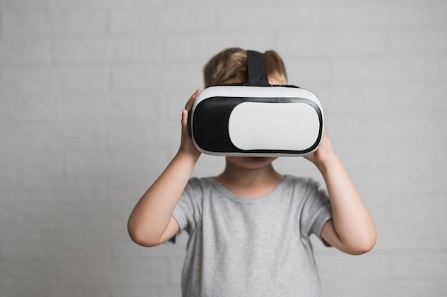 Junge, der mit kopfhörer der virtuellen realität spielt