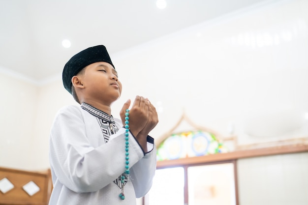 Junge, der mit offenem arm zu gott betet