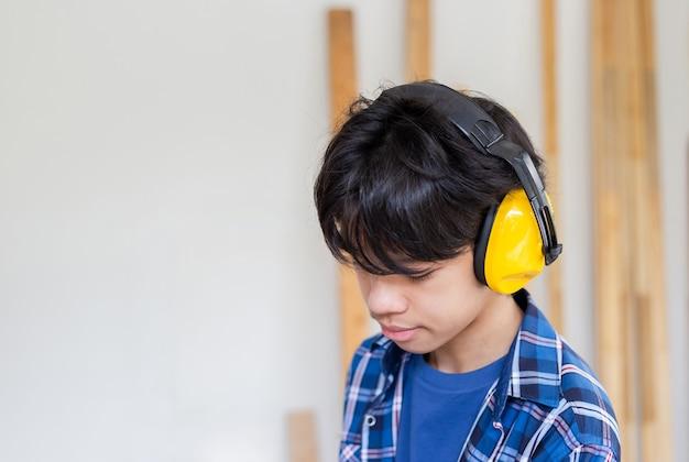 Junge, der mit ohrenschützern zur geräuschreduzierung in einer tischlerei steht. kinder lernen in der handwerkerwerkstatt
