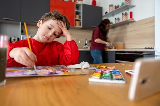 Junge, der mit online-fernunterricht mit smartphone zeichnet