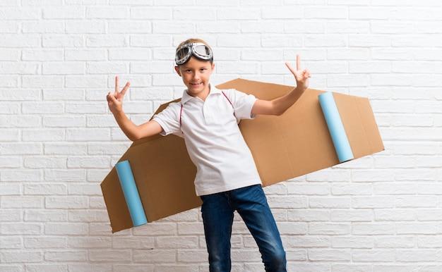 Junge, der mit pappflugzeugflügeln auf seinem zurück lächeln und zeigen des siegeszeichens spielt
