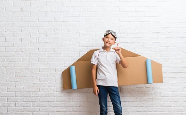 Junge, der mit pappflugzeugflügeln auf seiner rückseite steht und eine idee denkt
