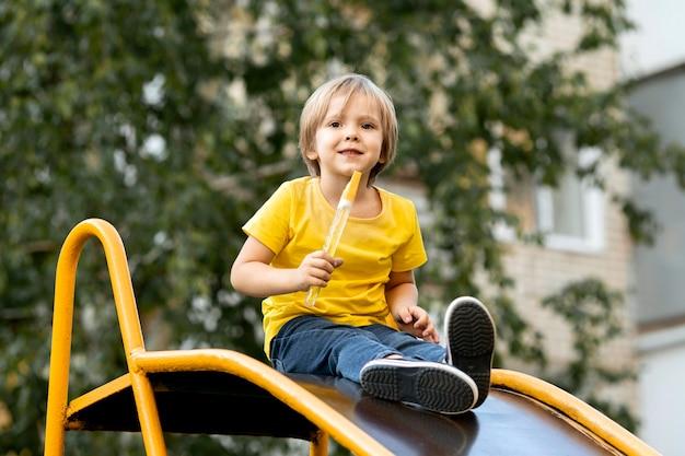 Junge, der mit seifenblasen im park spielt