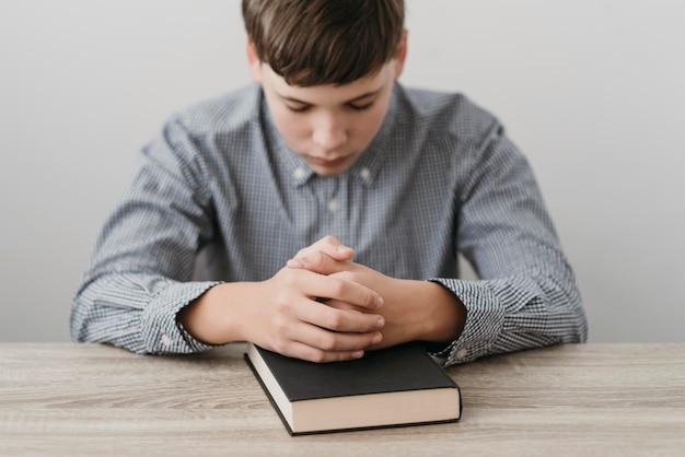 Junge, der mit seinen händen auf einer bibel betet