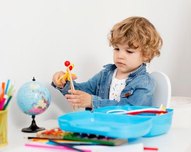 Junge, der mit spielzeug am schreibtisch spielt