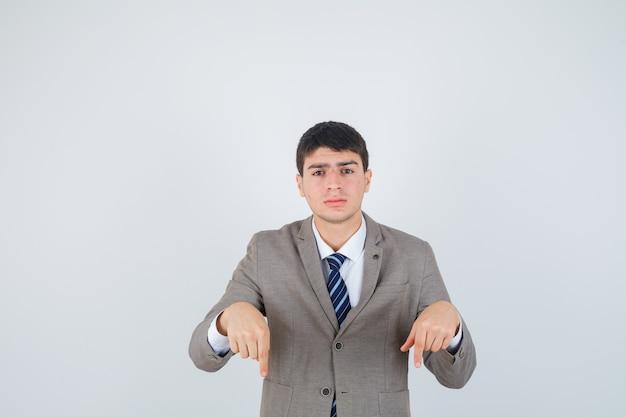 Junge, der mit zeigefingern im formellen anzug nach unten zeigt und ernst aussieht. vorderansicht.