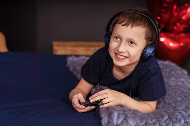 Junge, der musik in den kopfhörern liegen im bett hört