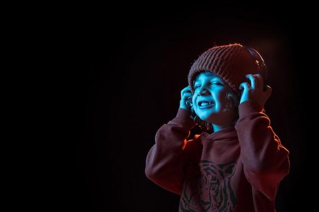 Junge, der musik in kopfhörern mit geschlossenen augen hört