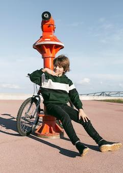 Junge, der neben teleskop draußen mit seinem fahrrad aufwirft