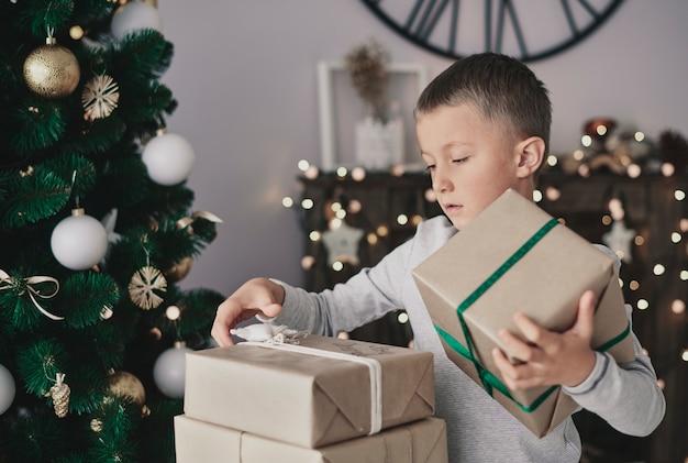 Junge, der neben weihnachtsbaum steht und geschenke nimmt
