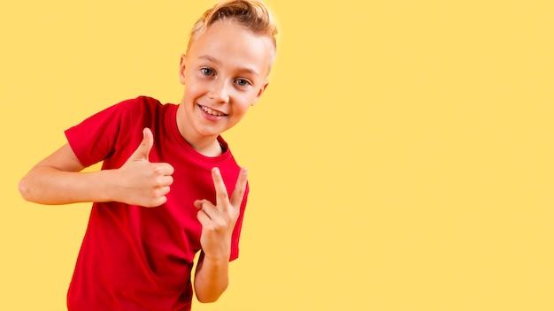 Junge, der okayzeichen und frieden mit kopieraum zeigt