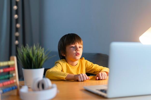 Junge, der online-kurse auf laptop hat