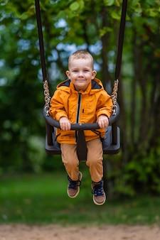 Junge, der orange regenmantel trägt, lächelt in schaukeln im park, fröhliche kindheit
