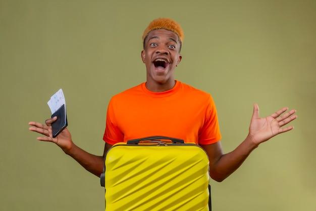 Junge, der orange t-shirt hält, das reisekoffer und flugtickets verrückt glücklich hält und über grüner wand steht