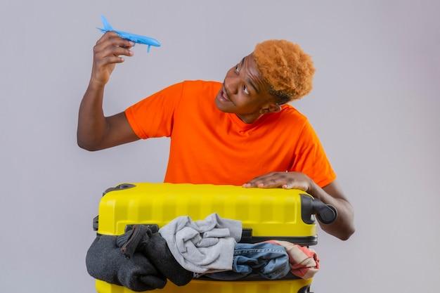 Junge, der orange t-shirt trägt, das mit reisekoffer voller kleidung steht und spielzeugflugzeug hält