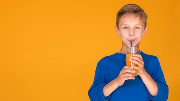 Junge, der orangensaft mit kopienraum trinkt
