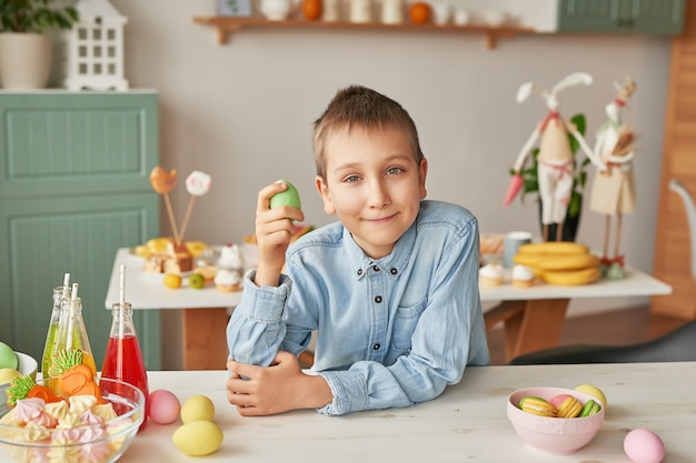 Junge, der osterei an der küche hält