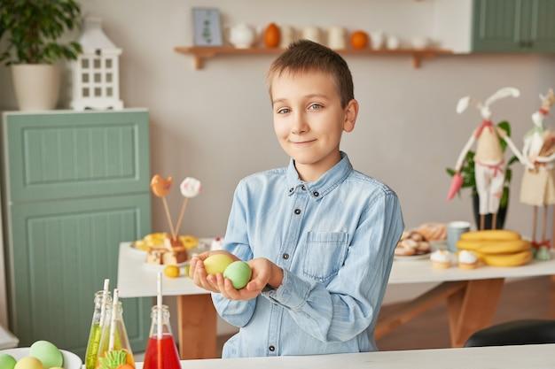 Junge, der ostereier an der küche hält