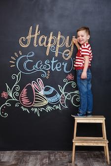 Junge, der osterkritzeleien auf kreide-tafel steht und zeichnet