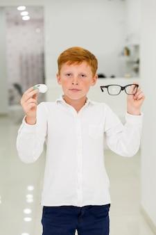 Junge, der plastikbehälter kontaktlinsen und brillen betrachten kamera hält