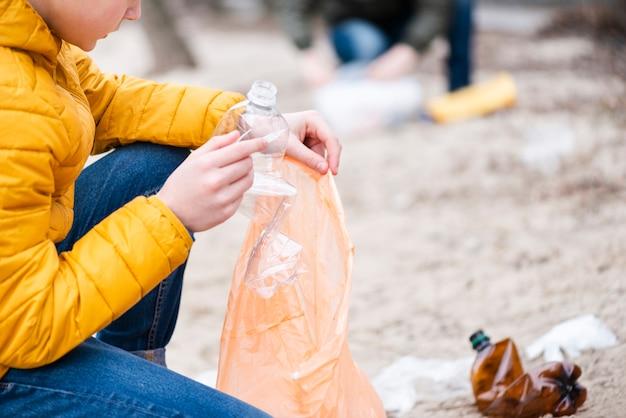 Junge, der plastikflasche in tasche setzt