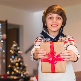 Junge, der präsentkarton zeigt