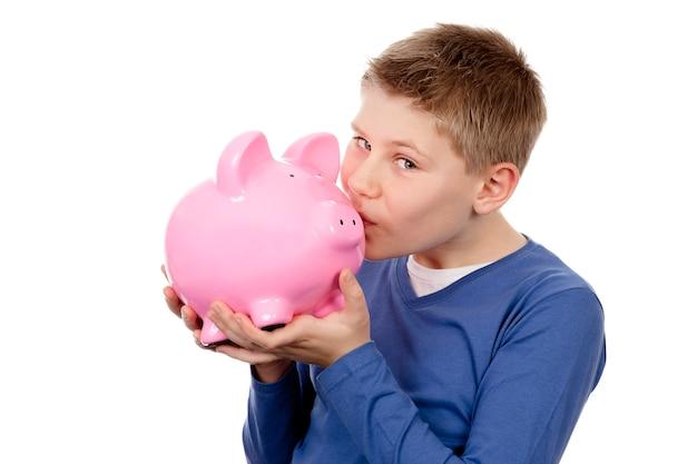 Junge, der rosa sparschwein auf weißem raum küsst