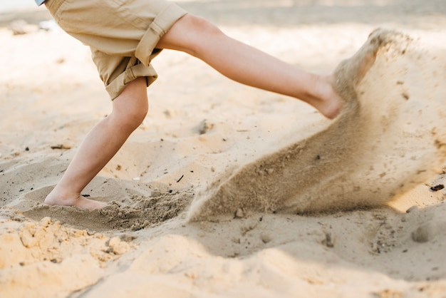 Junge, der sand am strand tritt