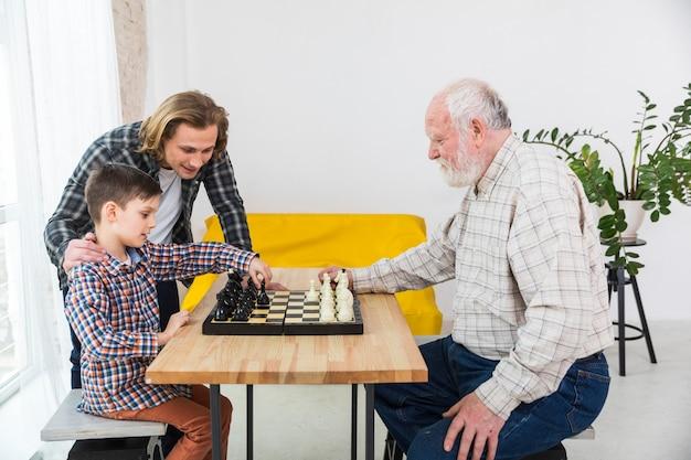 Junge, der schach mit großvater spielt