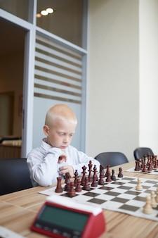 Junge, der schachspiel analysiert