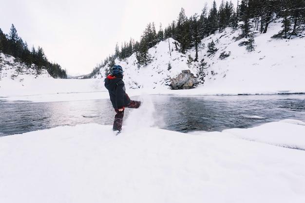 Junge, der schnee auf flussufer tritt