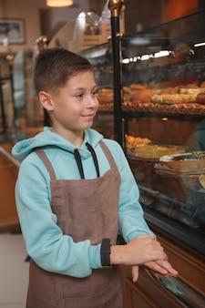 Junge, der schürze trägt, die an seinem elternbäckereigeschäft arbeitet