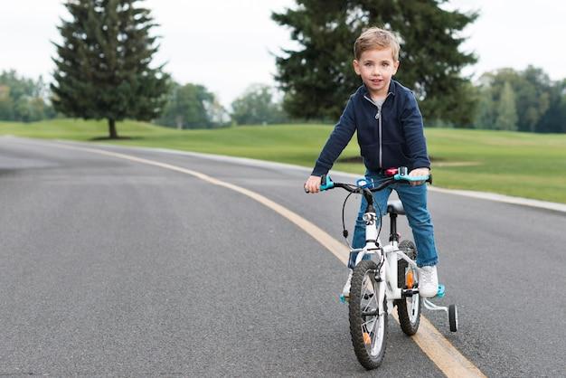 Junge, der sein fahrrad vorderansicht reitet