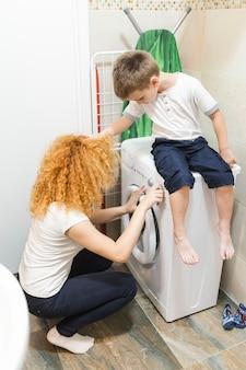 Junge, der seine mutter unter verwendung der waschmaschine betrachtet