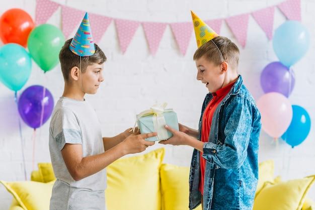 Junge, der seinem freund geburtstagsgeschenk gibt
