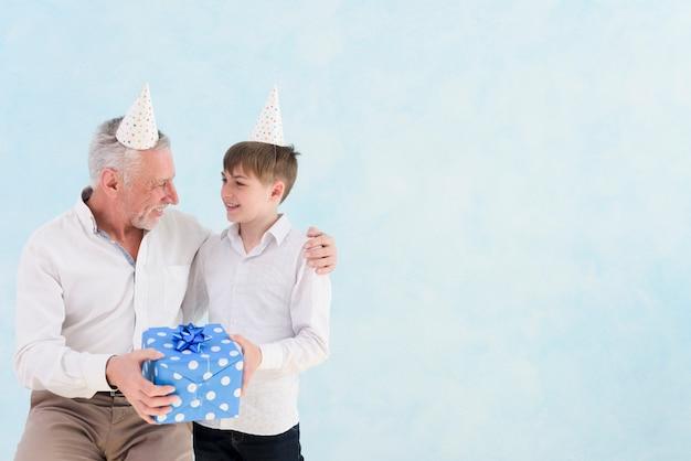 Junge, der seinem großvater an seinem geburtstag blaue geschenkbox gibt