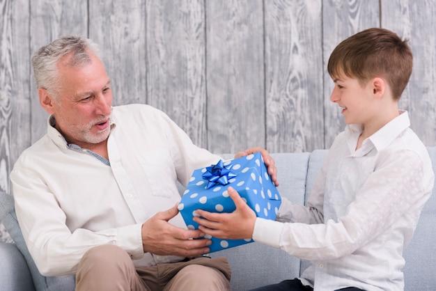 Junge, der seinem großvater blau eingewickelte geburtstagsgeschenkbox gibt