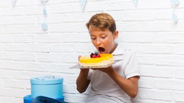 Junge, der seinen geburtstag feiert, den kuchen essend