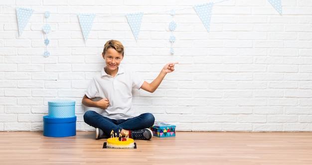 Junge, der seinen geburtstag mit einem kuchen feiert, der finger auf die seite zeigt und ein produkt darstellt