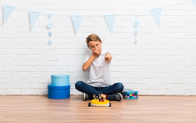 Junge, der seinen geburtstag mit einem kuchen feiert, der mit dem finger auf jemand zeigt und viel lacht