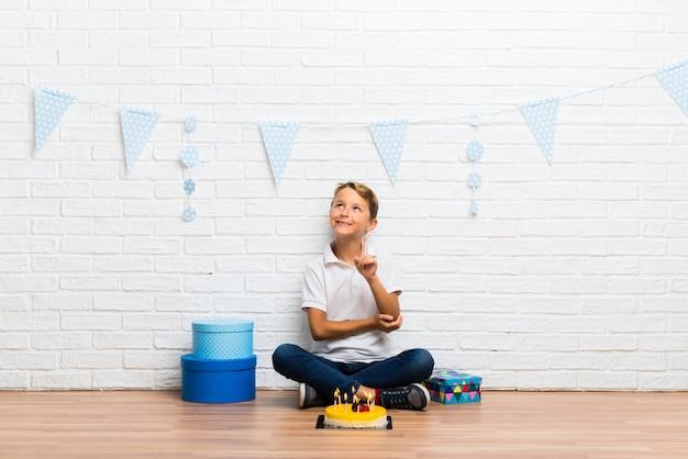 Junge, der seinen geburtstag mit einem kuchen feiert, der mit dem zeigefinger eine großartige idee zeigt