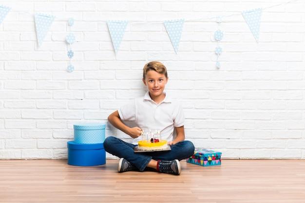 Junge, der seinen geburtstag mit einem kuchen feiert, der mit den armen an der hüfte aufwirft