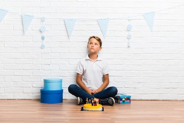 Junge, der seinen geburtstag mit einem kuchen feiert, der zweifel hat und mit verwirrtem gesichtsausdruck