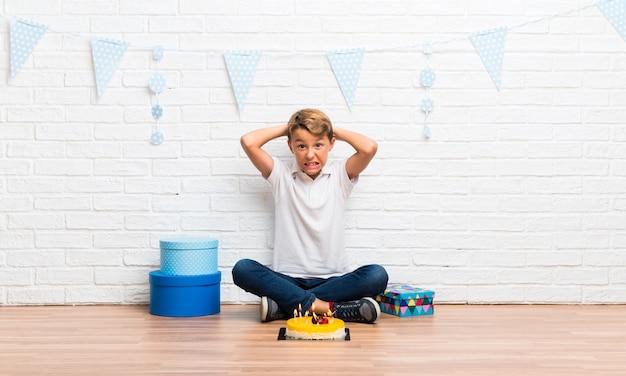 Junge, der seinen geburtstag mit einem kuchen mit etwas unglücklich und frustriert feiert.