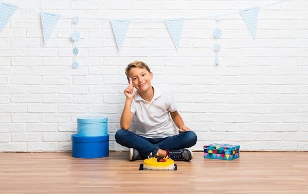 Junge, der seinen geburtstag mit einem kuchen zählt zeichen der nr. eine feiert