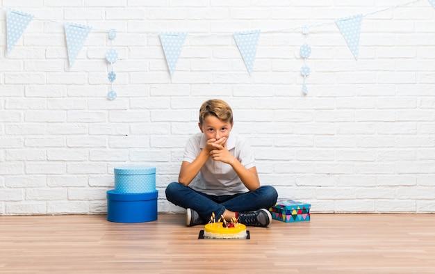 Junge, der seinen geburtstag mit einem kuchenbedeckungsmund mit den händen feiert
