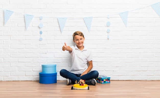 Junge, der seinen geburtstag mit einem kuchengeben daumen oben geste und lächeln feiert