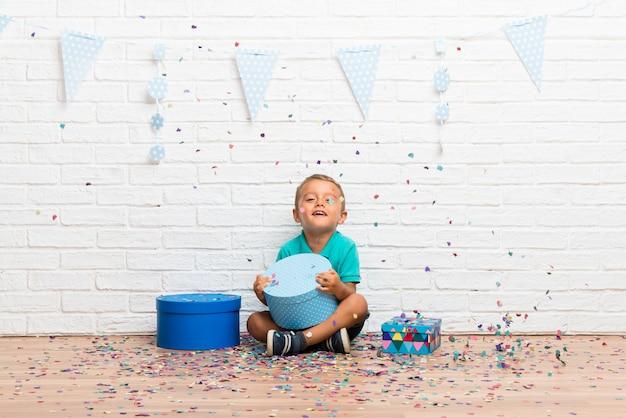 Junge, der seinen geburtstag mit konfetti in einer party feiert