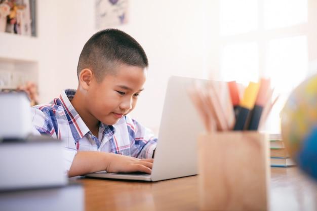 Junge, der seinen laptop verwendet, um online zu lernen.