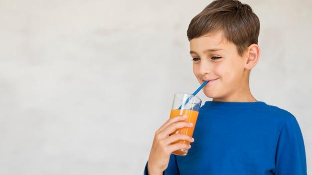 Junge, der seinen orangensaft mit kopienraum genießt
